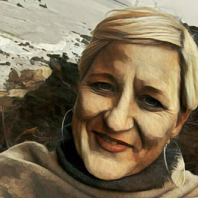A photo of gs practitioner Sue Kuyper. A white person with short blond hair and wearing a grey sweater and silver hoop earrings is smiling into the camera. Behind her is the ocean and a rocky beach and a grey sky. The whole picture has a watercolor filter on top of it.