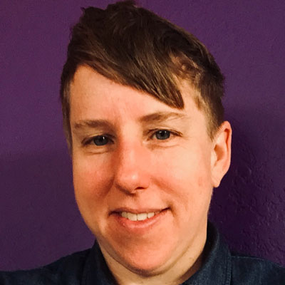 A photo of gs practitioner and teacher Amanda Ream. A white person with short hair, and bangs that swoop to the right of the photo is smiling into the camera. They are wearing a dark blue shirt and are in front of a wall that has been painted a deep shade of purple.