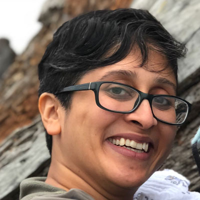 A photo of gs practitioner Bhavana Nancherla. A brown person with short salt and pepper grey and black hair is looing into the camera and smiling. They are wearing black-rimmed glasses and a green sweater and standing in front of grey and copper colored rock faces that are blurred in the background.