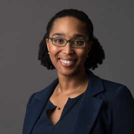 A photo of gs practitioner Kira Banks. A black woman with black rimmed glasses and curly hair pulled back is smiling into the camera. She is wearing a blue suit and a necklace with a pendant on it and is standing infront of a dark grey background.