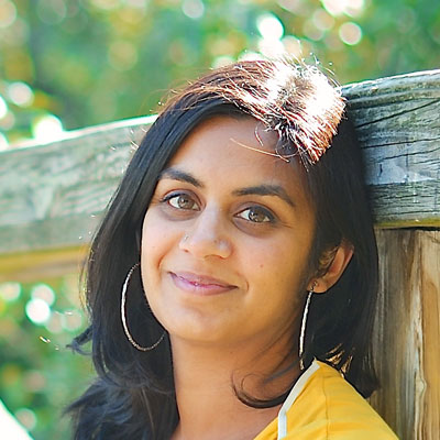 A photo of gs teacher and practitioner Fayza Bundalli. A brown woman with pink lipstick is leaning against a wooden railing with trees behind her. She is wearing pink lipstick, silver hoop earrings, and a yellow and white top.