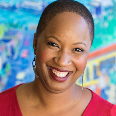 A photo of gs practitioner Sonya Brewer. A Black woman with short hair, dangly earrings, and wearing a red shirt with red lipstick is smiling into the camera. In the background is a multicolored wall, mostly shades of blue, some green, red, and yellow as well.
