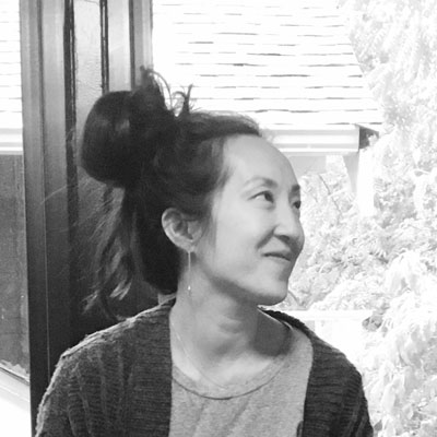 A photo of gs teacher Katelyn Song. A black and white photo of an Asian woman facing towards the right of the photo, wearing a dark cardigan over a light shirt with her long hair in a bun.