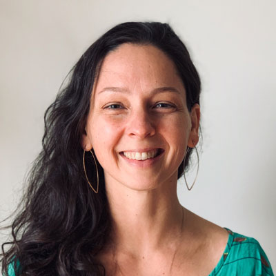 A photo of gs practitioner Becca Meredith. A white woman with long black hair, gold leaf-shaped hoop earrings, and a green shirt is smiling into the camera. Behind her is a white background.