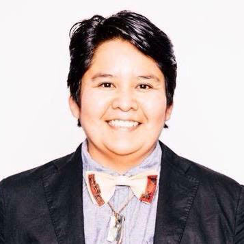 A picture of gs teacher and practitioner Nazbah Tom. A light brown person with their short black hair parted is smiling into the camera, wearing a blue button up shirt, a black jacket, and a white and red bowtie with a silver necklace underneath that.