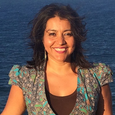 A photo of gs teacher and practitioner Donaji Lona Esteva. A brown woman is smiling into the camera with the ocean behind her. She is wearing a multicololored blue, orange, and black dress, red lipstick, and long gold earrings.