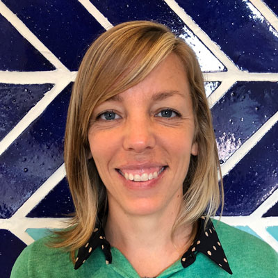 A photo of gs teacher and practitioner Hilary Moore. A white woman with medium-length blond hair smiles into the camera. She is wearing a green shirt with a black collar that has green polka dots. Behind her is a wall made of blue tiles and white grout.