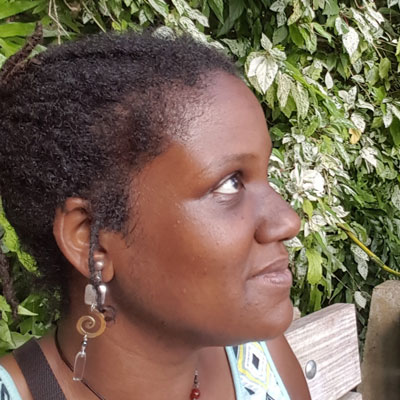 A photo of gs teacher and practitioner Lisa Thomas-Adeyemo. A black woman is looking up and to the right of the photo, with a smile on her face, her hair in dreadlocks, and wearing a dangly earring with a silver square, a copper spral, and a clear rectangle on it. Behind her is a bench and lush green bushes.