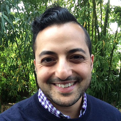A photo of gs teacher and practitioner Nathan Shara. A Brown man is smiling into the camera with short black hair slicked back and to the side and a small beard, wearing a blue sweater over a blue plaid collared shirt. Behind him is a grove of bamboo stalks.