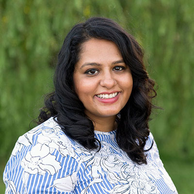A photo of gs practitioner Piya Banerjee. A brown woman with long wavy black hair and a floral white and blue top is smiling into the camera, with a green background.