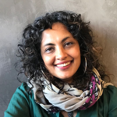 A photo of gs practioner Sumitra Rajukmar. A light-skinned brown woman with long curly black and brown hair, and wearing hoop earrings, a green top, and multi-colored scarf smiles into the camera.