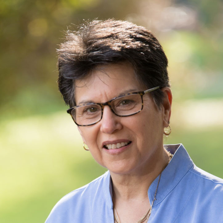 A photo of gs practitioner Denise Benson. A light-skinnned person with short hair and brown glasses is smiling into the camera. She is wearing a light blue shirt, and gold earrings and necklaces.