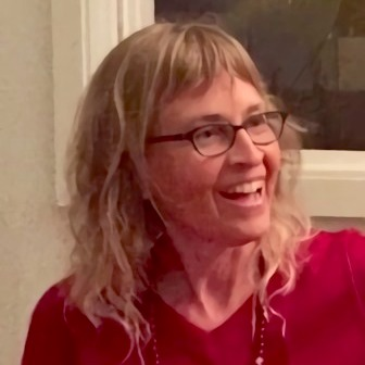 Picture of gs practitioner Vanissar Tarakali, a white woman with long blond hair infront of a white wall and window. She is wearing black rimmed glasses, red shirt, and brown beaded necklace and is facing to the right, and smiling.