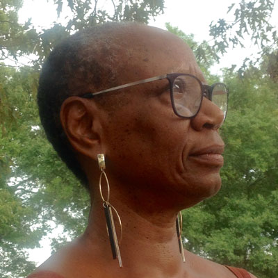 A photo of gs practitioner and teacher Alta Starr. A Black woman with short salt and pepper black hair is looking ahead of her, towards the right of the photo. She is wearing black-rimmed glasses, and long gold dangly earrings. Behind her is the sky and trees full of green leaves.