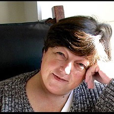 A photo of gs practitioner Donna Diamond. A white person with short hair is sitting in a black chair and resting her head on her hand. She is looking at and smiling towards the camera and is wearing a grey sweater over a white shirt.