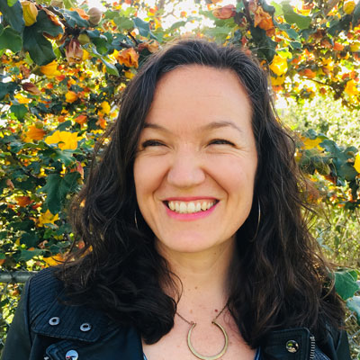 A photo of gs teacher and practitioner Lara Barth. A white person with long wavy black hair smiles and looks to the right of the photo. She is wearing gold hoop earrings and a gold necklace and a black jacket. Behind her are trees and a fence with yellow flowers.