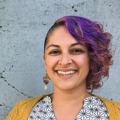 A photo of gs Program Associate, teacher, and practitioner Mahfam Malek. A light brown-skinned person is looking at and smiling into the camera. They have short hair on the sides and long curly purple and pink hair on the top. They are weaaring dangly earrings consisting of a crescents and diamond shaped metals and rocks, a black and white blouse and a mustard yellow cardigan. They are standing infront of a light grey wall.