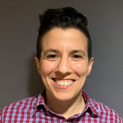 A photo of gs Resource Development Director and teacher, Danielle Feris. A white person with short black hair that is slightly longer on top is smiling infront of the camera. They are wearing a blue and red plaid button up shirt and are standing infront of a grey background.