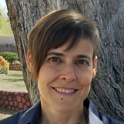 A photo of gs practitioner Jacks McNamara. A white person with asymmetrical brown hair is smiling into the camera. They are in front of a tree with grey bark and a wall and courtyard is behind them.