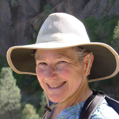 A photo of gs practitioner Elizabeth Ross. A white person is smiling into the camera, wearing a wide-brimmed light brown hat and a black backpack, and a blue shirt with a pattern on it.