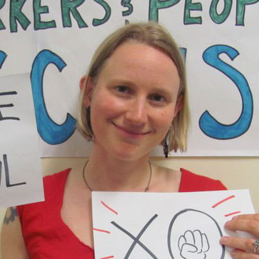 A photo of gs practitioner Clare Bayard, a white person with medium length blond hair smiling into the camera, wearing a red shirt, and holding up two hand drawn signs on paper.